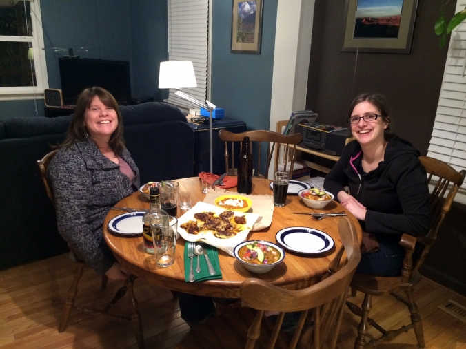 Margot and Emily sit for our finished product – llapingachos in the center, encebollados in the bowl, aguardiente already consumed.